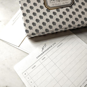 Mr. P's correspondence log to track your 8 note cards, on a marble table with the their signature anthemion printed note card packaging.