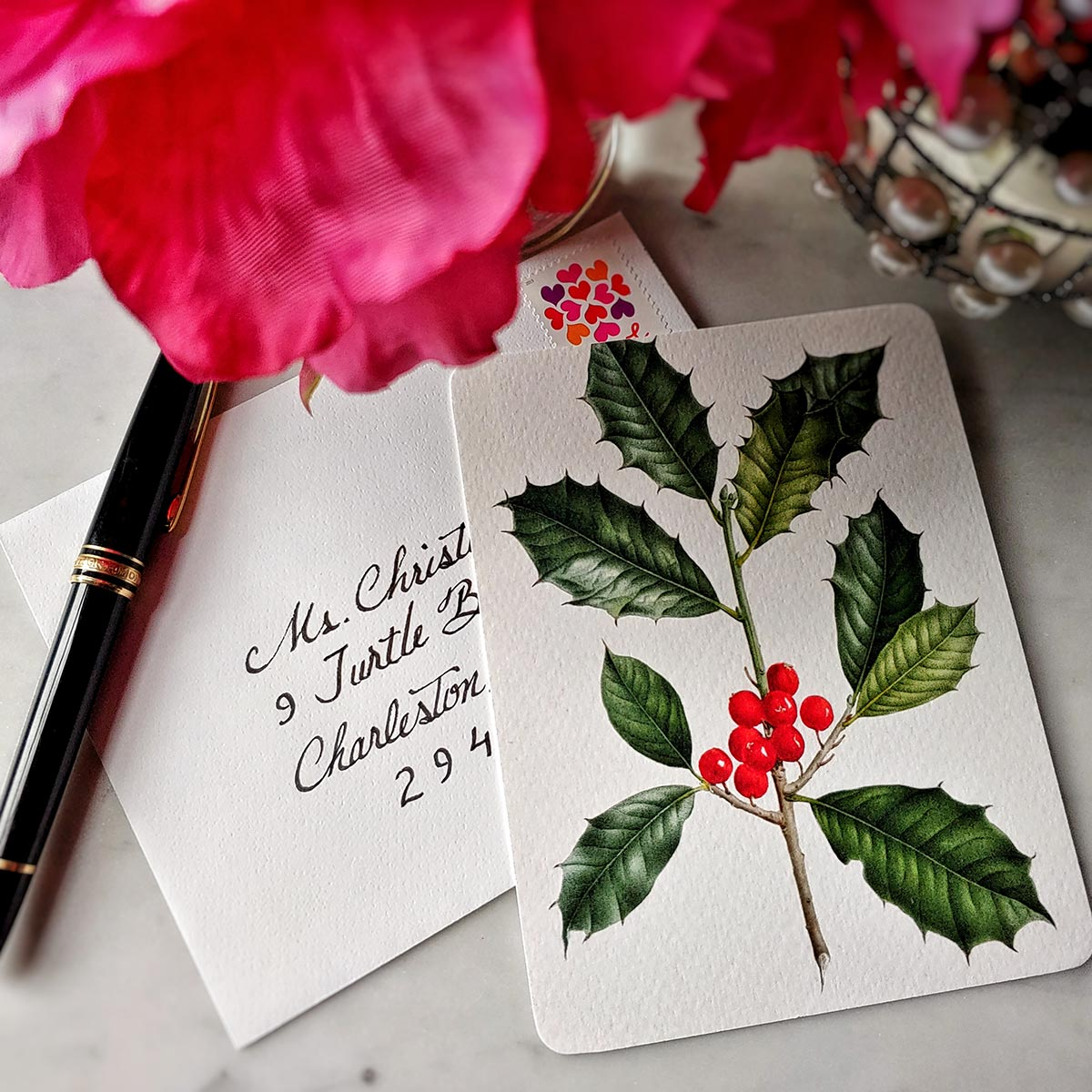 The Punctilious Mr. P's 'Holly' note card set on marble ledge with peony flower and fountain pen and addressed envelope