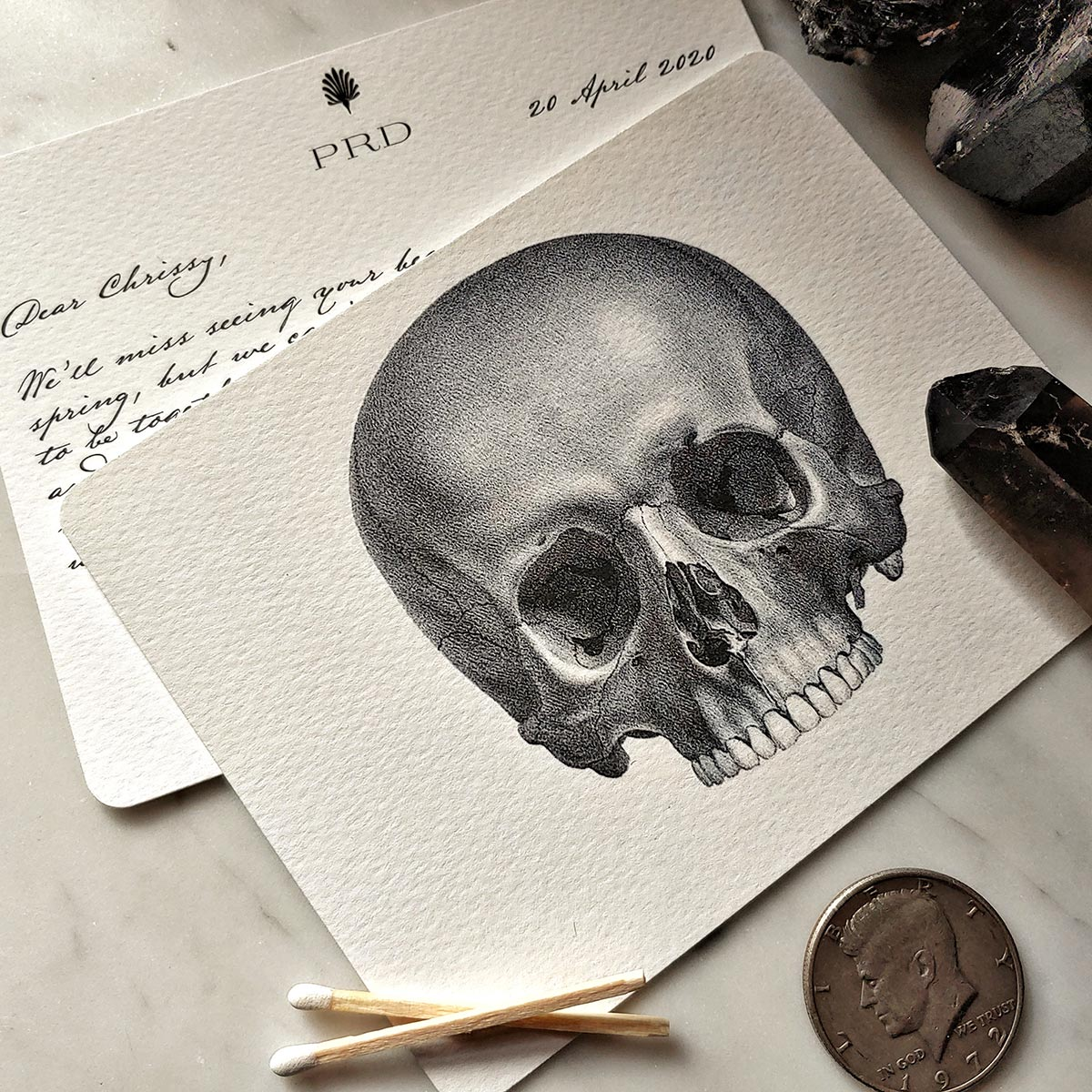 The Punctilious Mr. P's 'The Skull' note cards showing the message in old kinderhook fonto n marble table with beautiful crystals in background
