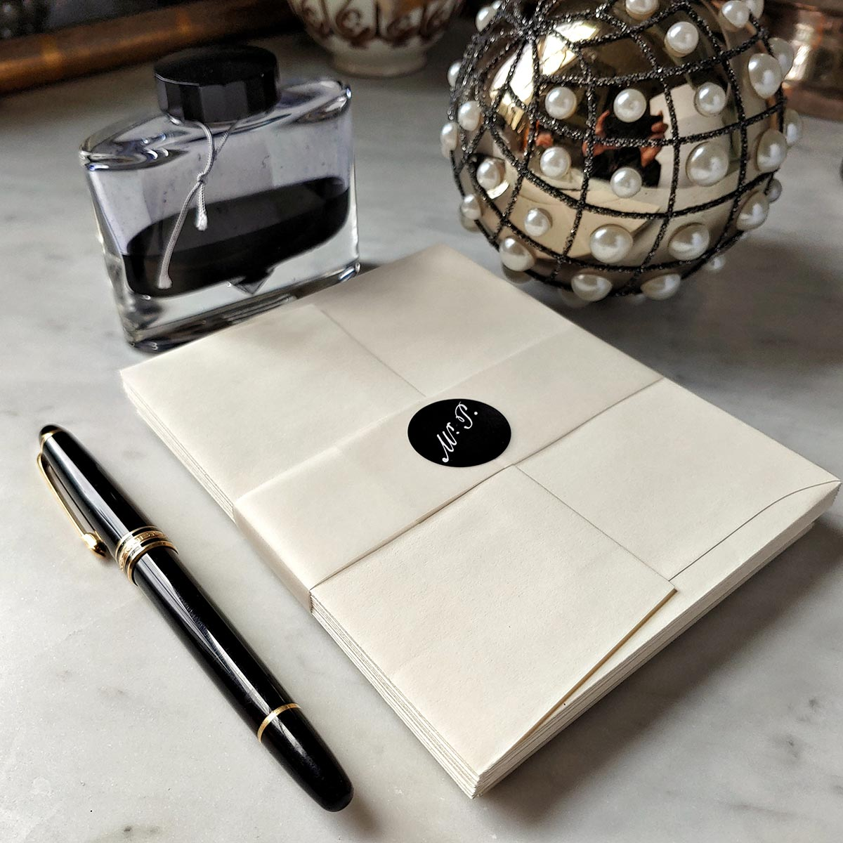 back view of The Punctilious Mr. P's Fine note cards on marble table with bottle of ink and fountain pen