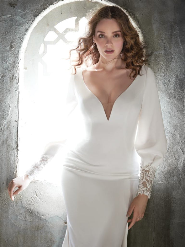 Gorgeous long-sleeved crepe wedding dress for the chapel of nature. Talin stretch crepe, Deep illusion V-neckline, Bishop long sleeves with lace cuffs, Lined with Donella crepe, Zipper closure with covered buttons trailing down to the hemline, Available in plus-size, Side slits in skirt.#utahbridalshop #weddingdresses #weddingaccessories #bridalcloset #classyweddings #brides #utahweddings #designerweddinggowns #gorgeousgowns #trendyweddingdresses #uniqueweddinggowns