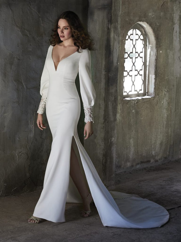 Long-sleeved crepe wedding dress for the chapel of nature. Talin stretch crepe, Deep illusion V-neckline, Bishop long sleeves with lace cuffs, Lined with Donella crepe, Zipper closure with covered buttons trailing down to the hemline, Available in plus-size, Side slits in skirt.#utahbridalshop #weddingdresses #weddingaccessories #bridalcloset #classyweddings #brides #utahweddings #designerweddinggowns #gorgeousgowns #trendyweddingdresses #uniqueweddinggowns