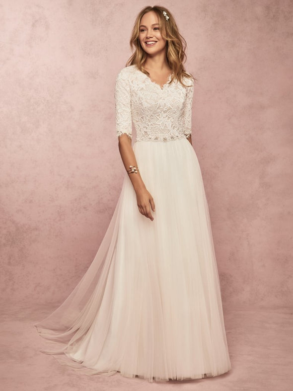 This soft and romantic modest wedding dress features an allover lace bodice with three-quarter sleeves, and a V-neckline. An attached beaded belt completes the sheath skirt, comprised of tulle. Finished with pearl buttons and zipper closure. #utahbridalshop #modestweddingdress #modest #quarterlengthsleeves #bridalshop #bridalcloset #weddinggown #bride #lacegown #weddingdress #templeready