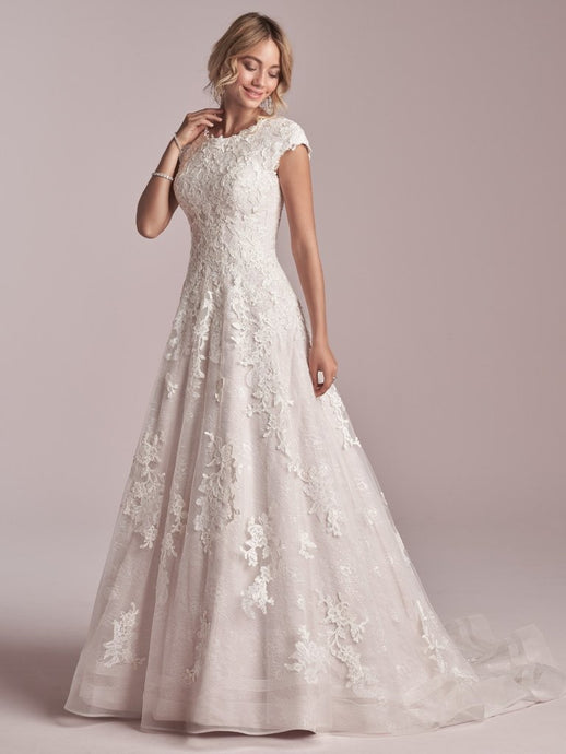 This modest cap-sleeved lace A-line wedding dress is classic, flattering, and fit for a princess. Additional coverage to our Courtney gown Sequined lace motifs over tulle and Lined lace cap-sleeves Lined with Virtue stretch jersey for comfort Pearl button over zipper closure Double horsehair hem finish Available in plus size. #utahbridalshop #weddingdresses #weddingaccessories #bridalcloset #classyweddings #brides #utahweddings #designerweddinggowns #modestgowns #trendyweddingdresses #uniqueweddinggowns