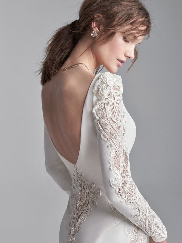 A long puff-sleeve V-back wedding gown for a sweet and sophisticated statement. Merona stretch crepe Soft V-back Deep illusion V-neckline Long Merona stretch crepe puff sleeves with illusion lace cut-out Lined with Serene stretch chiffon Crystal button over zipper closure#utahbridalshop #weddingdresses #weddingaccessories #bridalcloset #classyweddings #brides #utahweddings #designerweddinggowns #gorgeousgowns #trendyweddingdresses #uniqueweddinggowns
