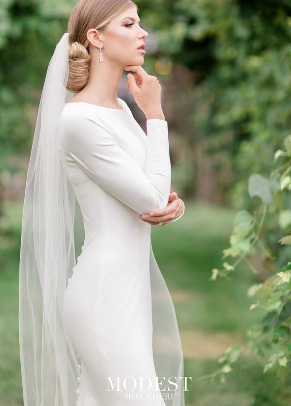 Your own royal moment in this simple and elegant stretch jersey trumpet gown featuring long sleeves, a bateau neckline, a dropped waist, princess seams, a zipper back with covered buttons down to the hem and a chapel train.#utahbridalshop #weddingdresses #weddingaccessories #bridalcloset #classyweddings #brides #utahweddings #designerweddinggowns #modestgowns #trendyweddingdresses #uniqueweddinggowns