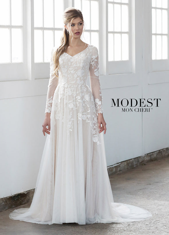 Stunning embroidered, sequin and beaded lace appliqués take center stage in this flowing tulle A-line gown with modesty cap sleeves under illusion lace long sleeves, a beaded curved slight V-neckline, a dropped waist, a concealed back zipper, and a softy gathered tulle skirt with a chapel train. Modest illusion long sleeve utah wedding gown #utahbridalshop #weddinggowns #sandyutah #bridalcloset #brides #bridalshop #utahwedding #designerweddings #templeready #weddingaccessories #modestweddingdress