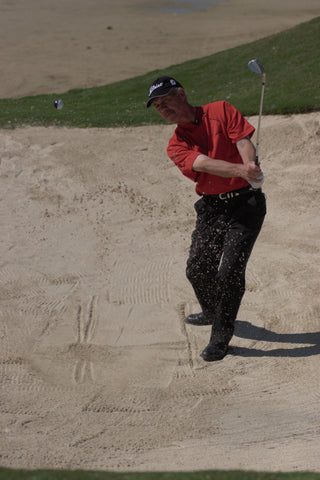 Pete Cowen wearing a red shirt, after hitting a golf ball in the sand.