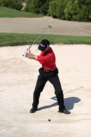 Pete Cowen preparing to hit golf ball in sand