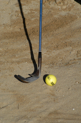 Golf club and yellow golf ball in sand