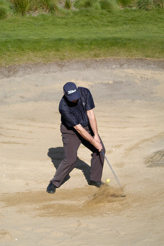 Mark Holland hits a golf ball in sand