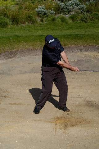 Mark Holland hitting a golf ball out of sand