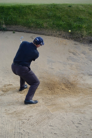 Mark Holland hitting a yellow golf ball out of sand