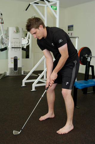 Man practising holding a golf club in a gym