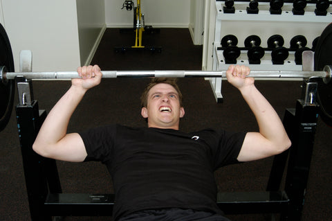 Man lifting weights over his head with a black shirt