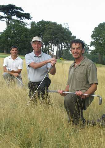Steve Gould and two men kneeling in grass