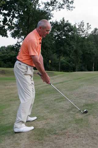 Keith Williams hitting a golf ball up the side of a small hill in an orange shirt.