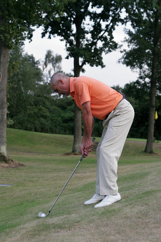 Keith Williams hitting a golf ball on the side of a hill in an orange shirt.