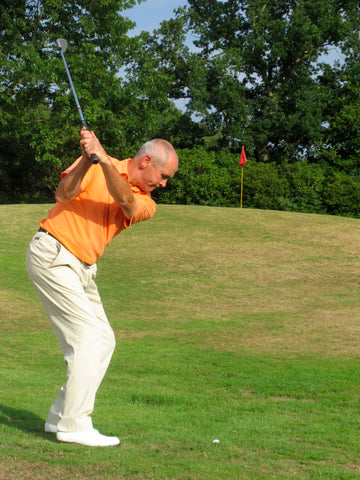 Keith Williams swinging a golf club back to hit a golf ball towards a red flag