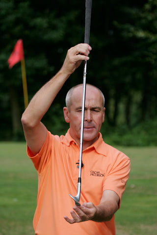 Keith Williams holding a golf club vertically in an orange shirt