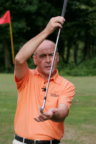 Keith Williams holding a golf club leaning forwards in an orange shirt