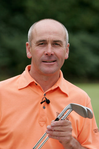 Keith Williams Profile in orange shirt with golf clubs