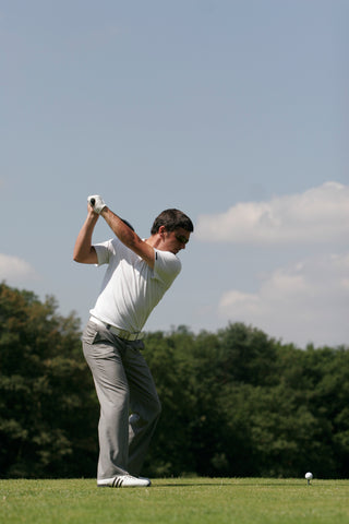 man preparing to hit a golf ball