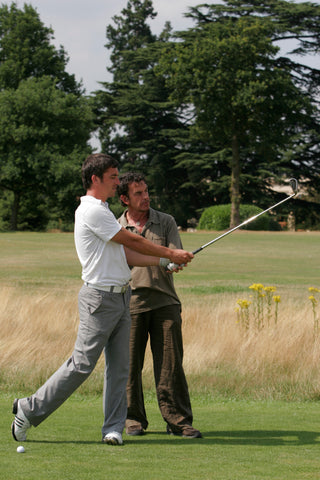 Steve Gould watching a man in white shirt practise with his golf club
