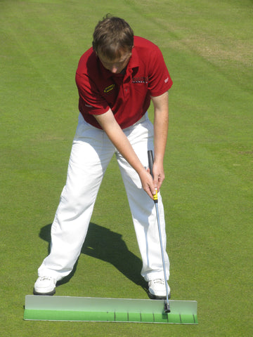 Man holding a golf club wearing a red shirt