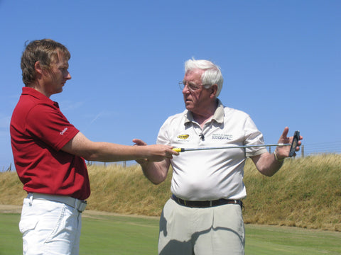 Harold swash talking to a man in a red shirt holding a golf club