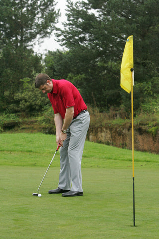 Karl Morris hitting a golf ball towards a yellow flag