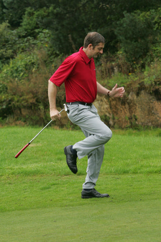 Karl Morris running on the spot with a golf club, in a red shirt.