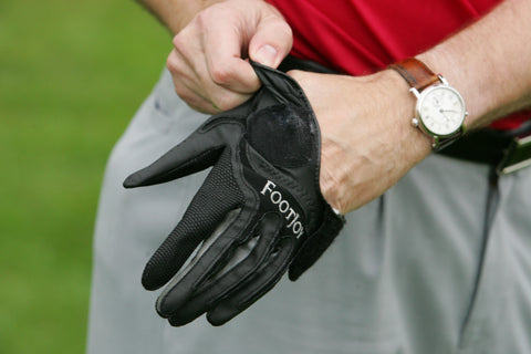 Man putting on a black golf glove with a red shirt and watch on