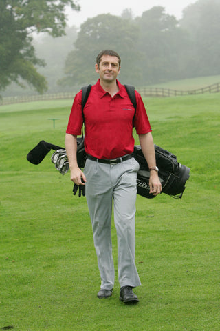 Karl Morris walking with a golf bag on his back and clubs