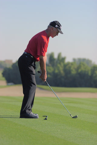 Peter Cowen in a red shirt preparing to hit a golf ball