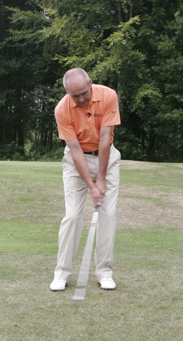 Kieth Williams swinging a golf club in an orange shirt