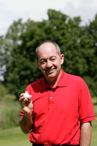 Denis Pugh profile in a red shirt holding a golf ball.
