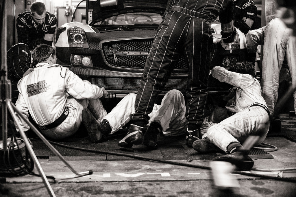 """This image shows a Spa 24 Hours race in 2011, where everyone in the whole team is working on the car to get it back out again. It took two hours to fix, but completed the 24 Hour race."" Photo by Lara Platman."