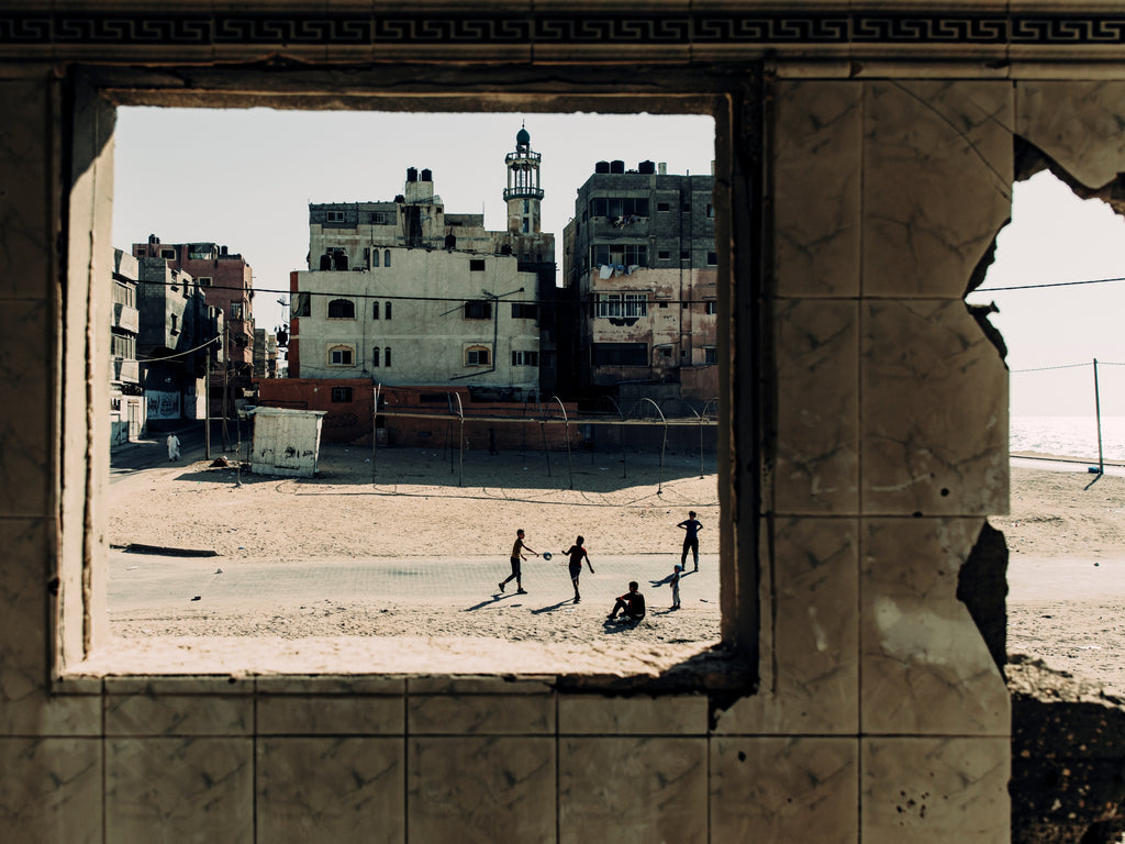 A window into the world of people in crisis - children play football on the beachfront in Gaza to a back drop of a shelled building. © Paddy Dowling/EAA