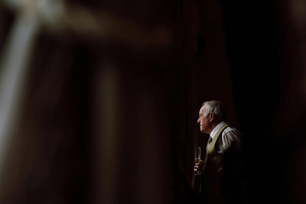 The magic of the silent shutter allows an emotional father of the bride to have his moment of reflection during bridal prep without being distracted or even knowing that he's being photographed – Photo by Chris Johnson.