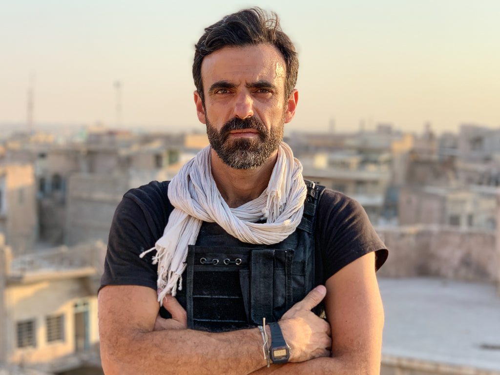 Paddy Dowling standing on the rooftop of a bombed school in Mosul. The risk here is unexploded bombs in the rubble and getting shot by snipers. Photo by David Bird.