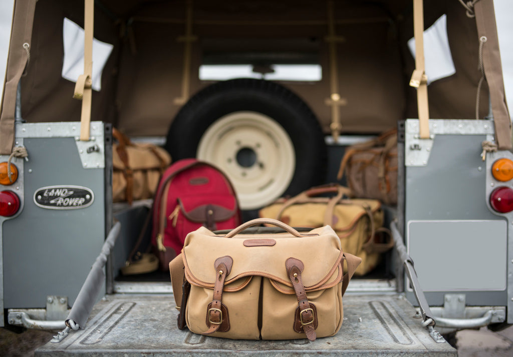 1964 Series 2a Land Rover with Billingham Billingham Hadley Pro bag (front), Rucksack 35 in Burgundy Canvas and Chocolate Leather (centre left), 550 bag (rear left), Billingham 225 bag (centre right) and old Billingham System bag (rear right). Photo by Lara Platman.
