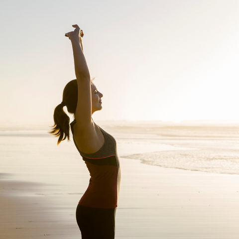 lady stretching with her hands up at the beach
