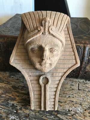 A hand-carved wooden Egyptian pharaoh head plaque