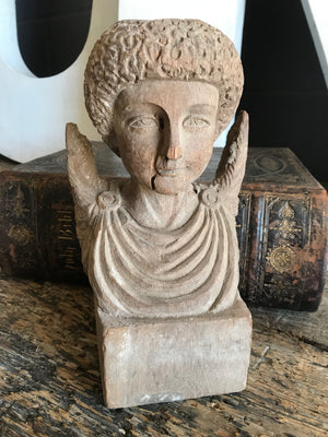 A hand-carved wooden cherub bust