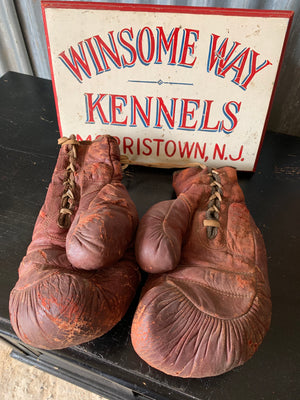 A vintage pair of large red leather boxing gloves