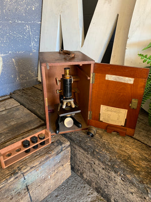 A Watson Service brass monocular microscope in original wooden case