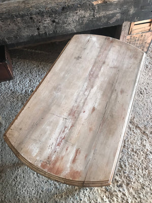 A drop leaf circular bleached pine painted table on castors
