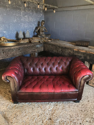 An oxblood two seater Chesterfield sofa with button back and seat