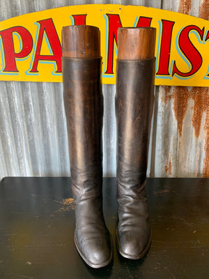 An old pair of black leather riding boots with wooden lasts